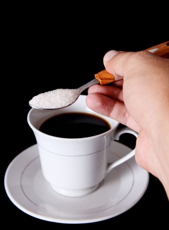 White cup of coffee and a hand holding a spoon with sugar photo