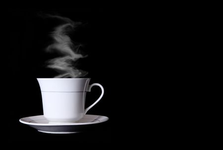 White cup of coffee with smoke over black background photo