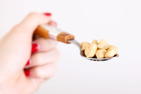 Hand holding a spoon with peanut over white background photo
