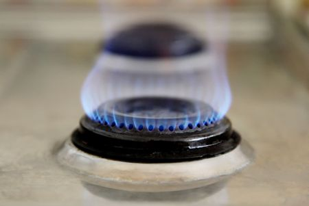 burner: Blue flame of an old gas stove. Side view Stock Photo