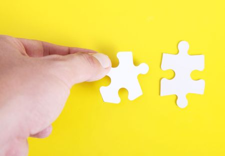 One hand clasping pieces of a puzzle over yellow background photo