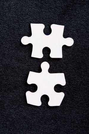 Two pieces of a puzzle on a black background Stock Photo - 6268399