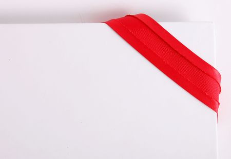 Red ribbon on cardboard over white background. Blank image to insert text or design photo