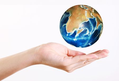 Womans hand holding a levitating world over white background photo