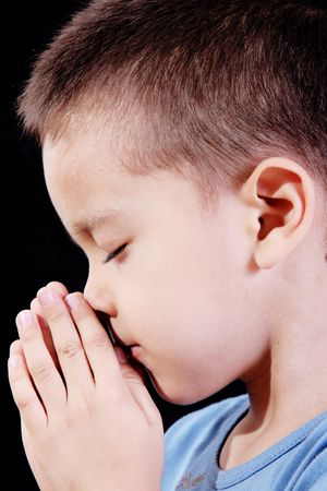 Child praying over black background. Beauty image photo