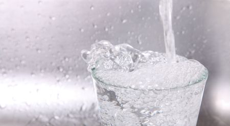 Water falling into a glass over chrome background Stock Photo - 6287172