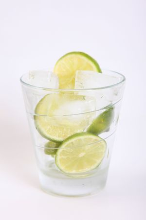 Glass with lime and ice over white background photo
