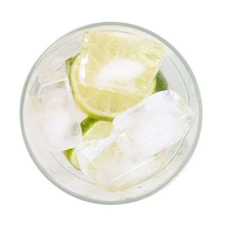 Glass with lime and ice over white background. High view photo