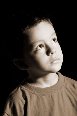 serious face: Child looking up with hope, over black background