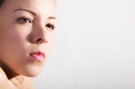 Face of young woman over gray background. Looking at camera photo