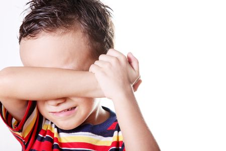 child crying: Child crying covering his face with his hand.