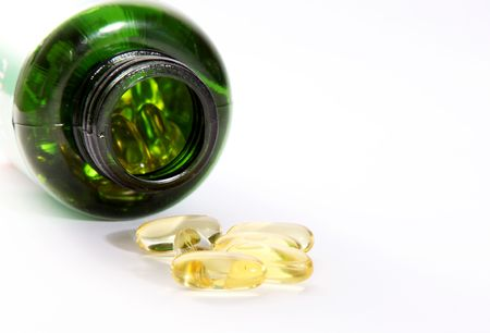 yellow pills and green bottle on light background  Stock Photo - 6688376