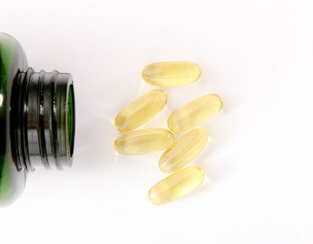 yellow pills and green bottle on light background Stock Photo - 6688380