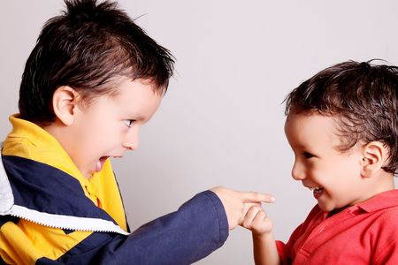 Children pointing and playing happily over gray background Stock Photo - 6676122