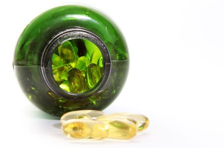 yellow pills and green bottle on light background   Stock Photo - 6688378