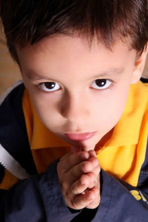 Child praying  and looking up with blue and yellow jacket  photo