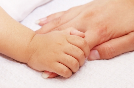 baby taking his mothers hand. white background photo