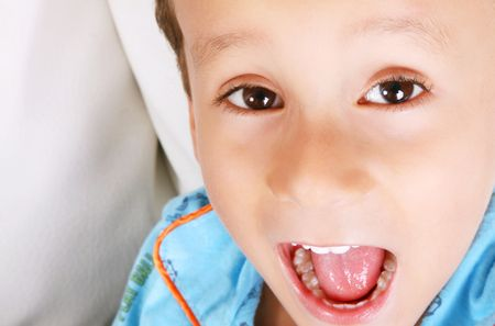 Child looking at the camera playing and shouting. Face close up photo
