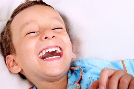 pijama: Ni�o de cuatro a�os de edad, riendo sobre fondo blanco. Concepto de felicidad Foto de archivo