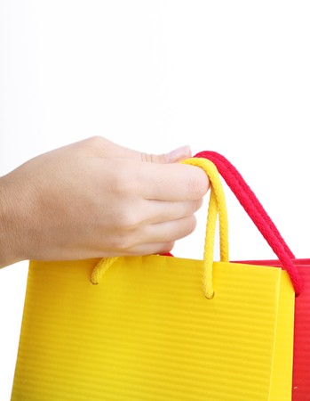 Hand holding a shopping bag over white background photo