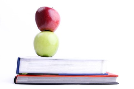 Green and red apple above books. Concepts: wisdom, knowledge and education photo