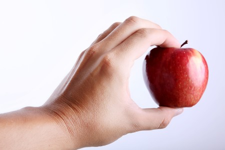 Red apple on hand over white background photo