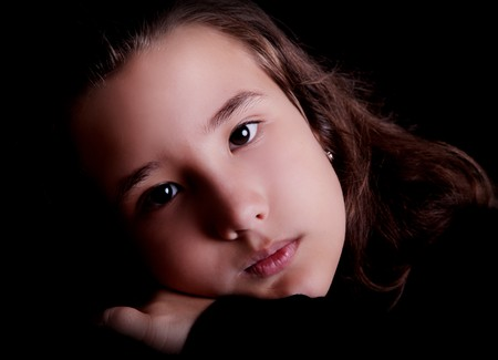 Serious young girl over black background. Child portrait photo