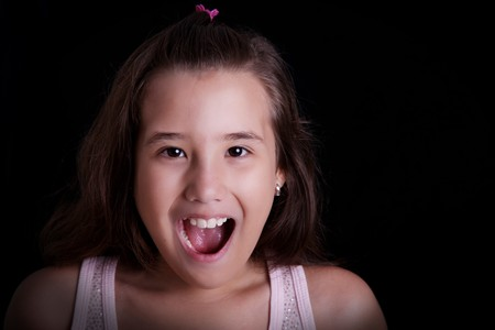 Girl screaming on a black background. Ten years old photo
