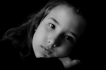 ifestyle: Ten years old serious girl looking at the camera. Black and white image