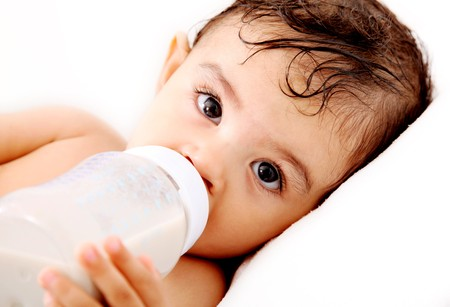 赤ちゃんのミルクを飲むと、カメラを見てします。白の背景 写真素材