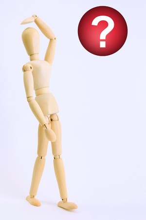 Wooden doll looking a red question symbol Stock Photo - 7549677