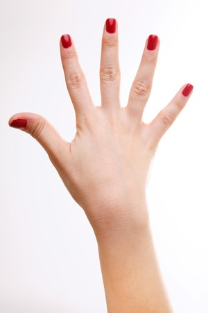 Womans hand with nail polish on white background photo