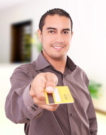 Young man smiling and giving his credit card photo