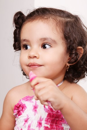 Two year old girl playing with lipstick Stock Photo - 8092410