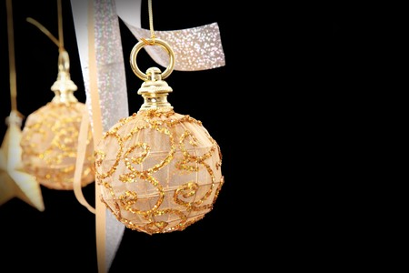 Golden christmas ball on black background, space to insert text or design photo