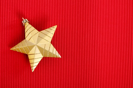 Gold Christmas star over red background. Xmas Card photo