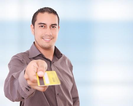tarjeta visa: Joven dando su tarjeta de cr�dito en la c�mara, fondo azul Foto de archivo