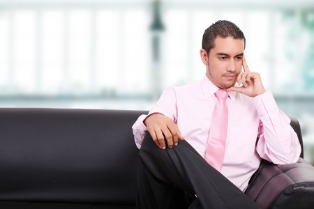 Businessman thinking on a sofa, indoor image photo