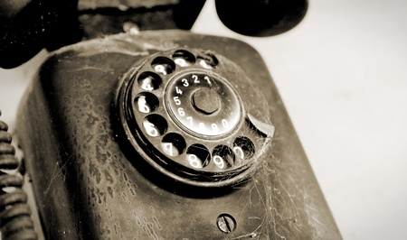 Black disc phone on white wall, vintage object Stock Photo - 8305565