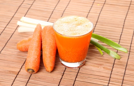 Carrot juice with vegetables over bamboo background Stock Photo - 8305605