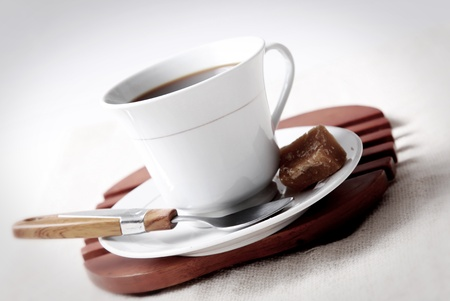 cup of coffee with brown sugar on a wooden board over white background photo