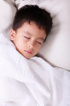 ni�o durmiendo: Ni�o de cinco a�os de edad, durmiendo con manta blanca Foto de archivo
