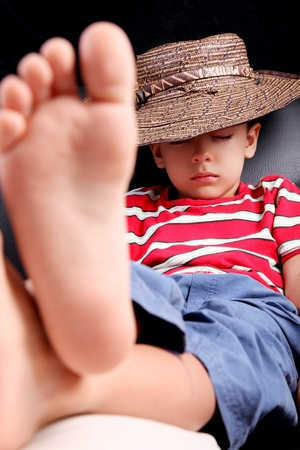kid feet: Five years old child sleeping with hat comfortably