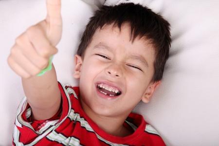 positivism: Ni�o feliz miente y mostrando su pulgar como un signo de positivismo