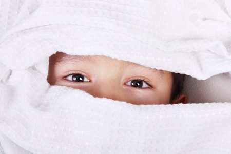 Child covering his face with a white cloth, leaving his eyes uncovered photo