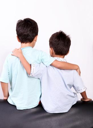 dos niños abrazando a hacer sobre fondo blanco Foto de archivo