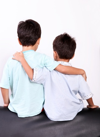 two children hugging back over white background Stock Photo - 8646444