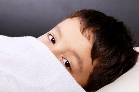 Child slept with the blanket in the face, looking at camera photo