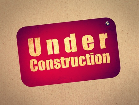 Red billboard with under construction text over wooden background photo
