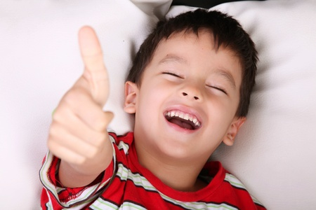 positivity: Child smiling and expressing positivity on white background